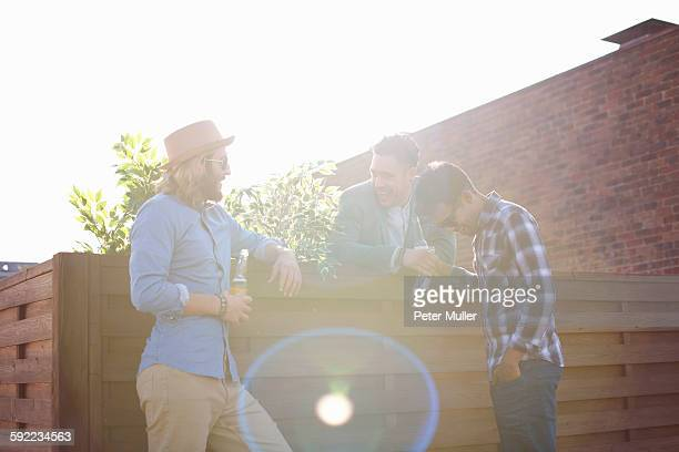 Three male friends chatting and drinking beer at rooftop party