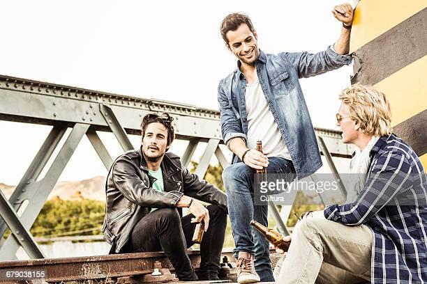 Three male friends chatting on rural railway bridge track, Franschhoek, South Africa