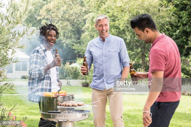 Three male friends having barbecue and drinking beers