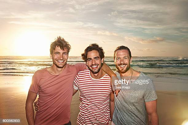 three male friends on beach, smiling - arm around stock pictures, royalty-free photos & images