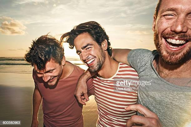three male friends on beach, smiling - três pessoas imagens e fotografias de stock