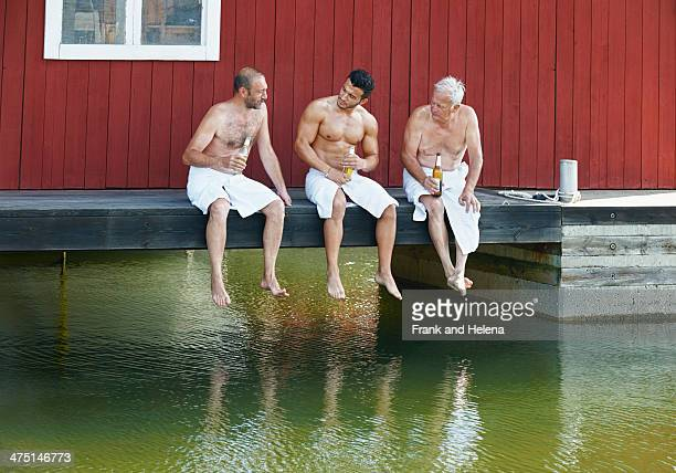 Three male friends sharing a beer outside sauna