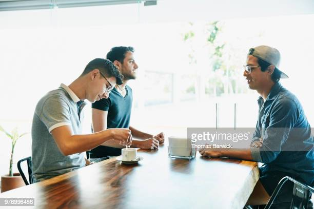 three male friends sitting at counter in bakery sharing coffee - só homens jovens imagens e fotografias de stock
