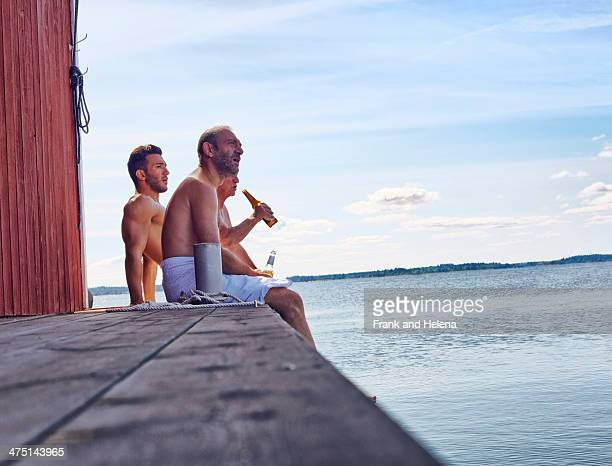 Three male friends sitting outside sauna enjoying beer