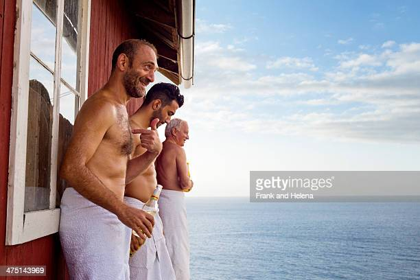 Three male friends standing outside sauna enjoying beer