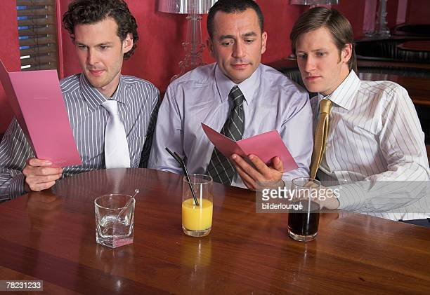 three male friends studying menu in restaurant together