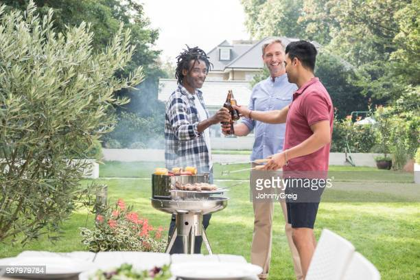 Three male friends toasting beer bottles in garden with bbq