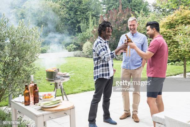Three male friends toasting with beer bottles by barbecue