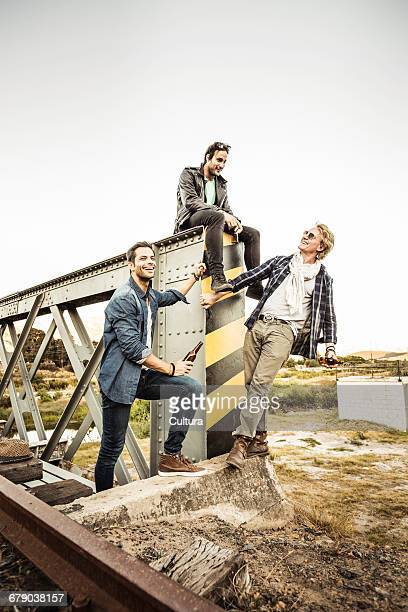 Three male friends with bottled beer on rural railway bridge, Franschhoek, South Africa