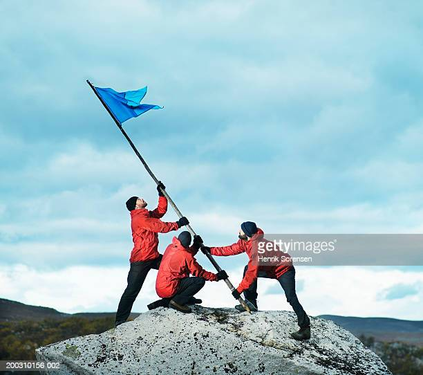 Three male hikers raising flag on rock