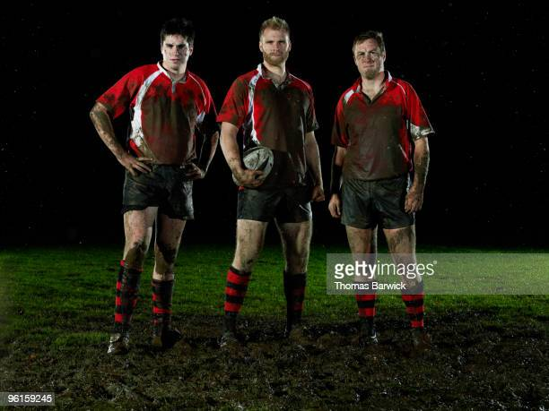 three male rugby players covered in mud - rugby team stock pictures, royalty-free photos & images