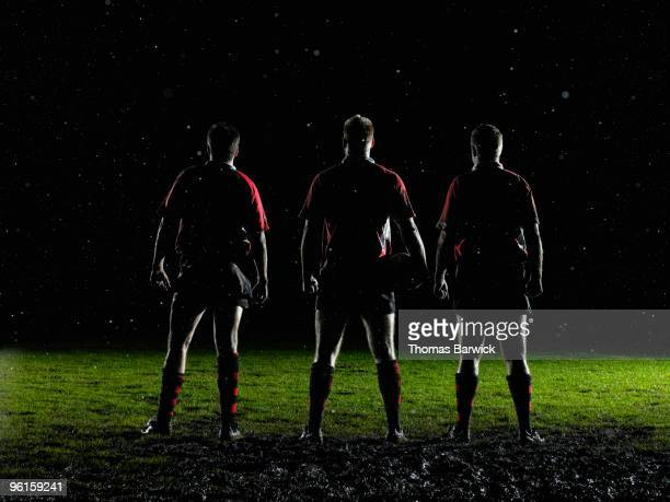 three male rugby players standing in rain on field - チームスポーツ ストックフォトと画像