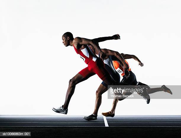 three male runners crossing finish line - finish line stock pictures, royalty-free photos & images