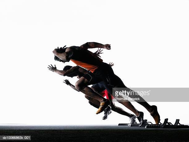 three male runners leaving starting blocks, side view - beginnings stock pictures, royalty-free photos & images