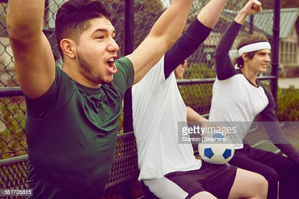 Three male soccer player spectators celebrating