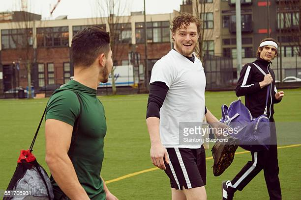 Three male soccer players carrying gym bags on soccer pitch