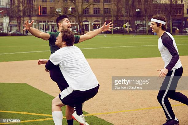 Three male soccer players celebrating on soccer pitch