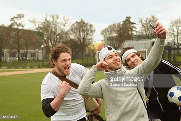 three male soccer players taking celebration smartphone selfie - exhibitionniste photos et images de collection