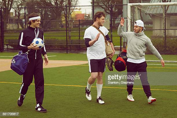 Three male soccer players walking and talking on soccer pitch