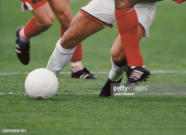 three male soccer players with ball, low section - low section stock pictures, royalty-free photos & images