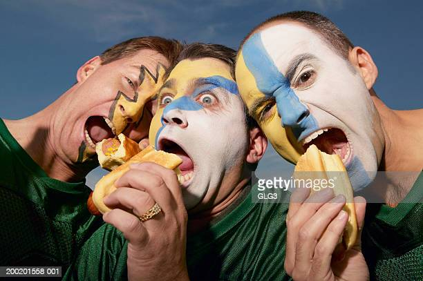 three male sports fans eating hot dogs - football body paint stock photos and pictures