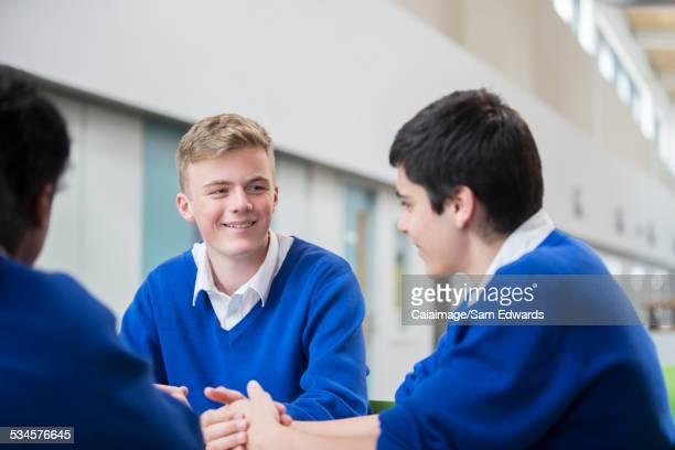 Three male students wearing blue school uniforms talking in corridor