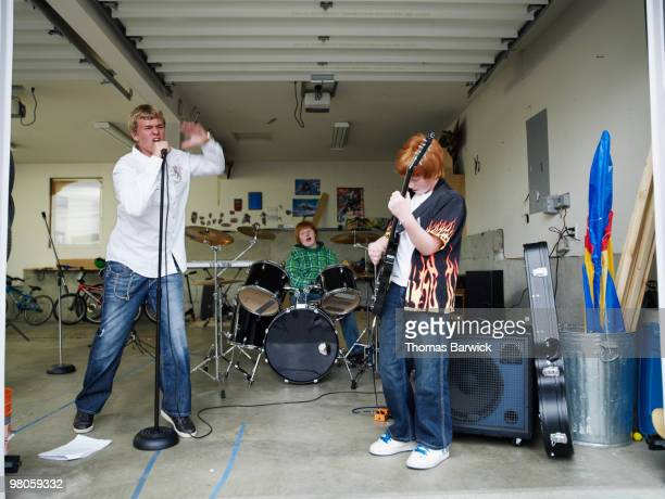 three male teenagers playing music in garage - garage band stock photos and pictures