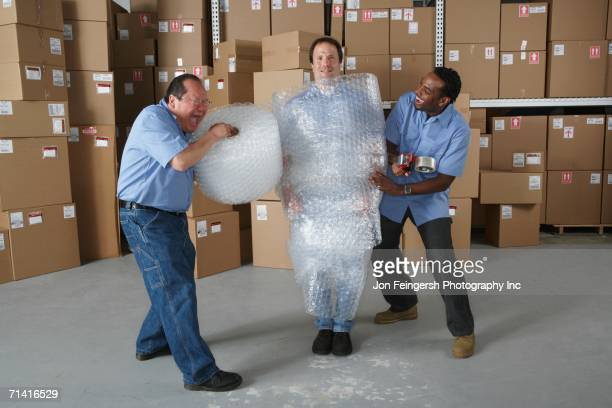 three male warehouse workers joking around - eingewickelt stock-fotos und bilder