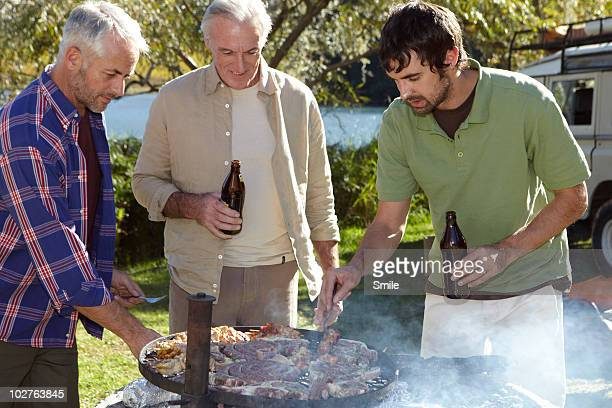 Three man barbecuing at camp site