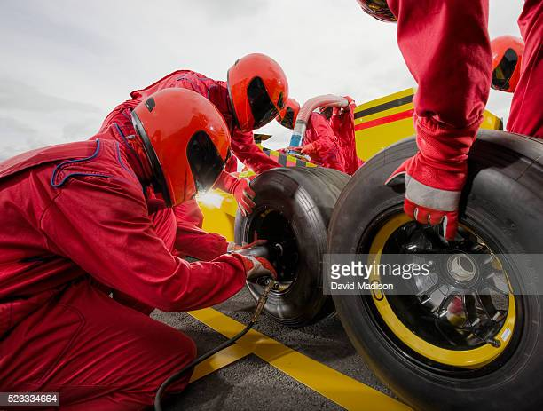 three man team changing tire on formula one racecar - pit stop stock pictures, royalty-free photos & images