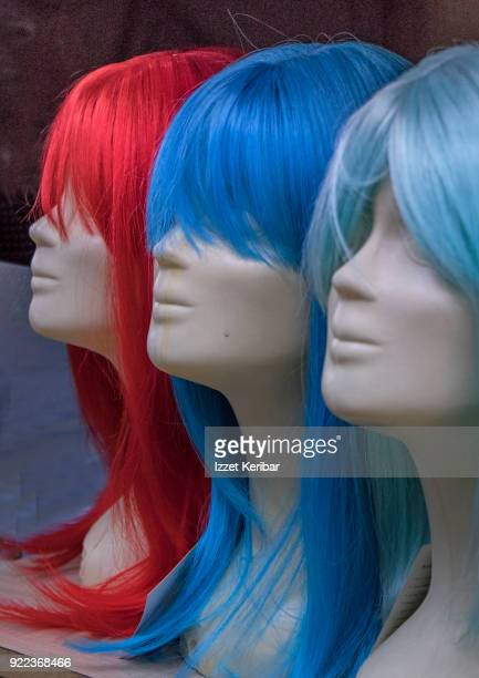 three mannequin heads wearing wigs with bright colors.