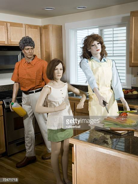Three mannequins portraying a family in the kitchen