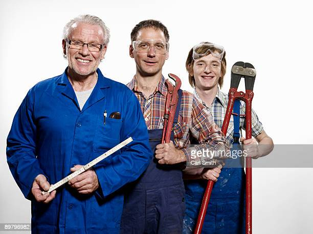 Three manual workers holding tools