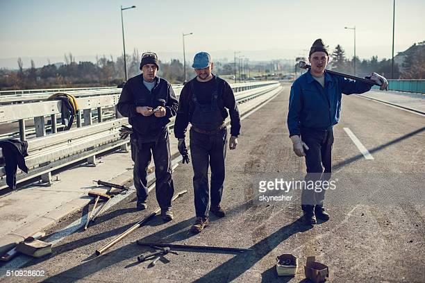 Three manual workers walking on a road.