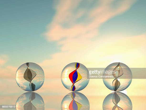 Three marbles on a reflective surface