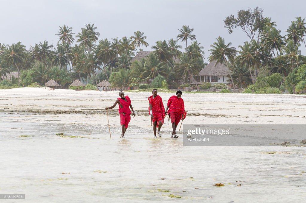 Three Masai warriors walking on the beach : Stock Photo