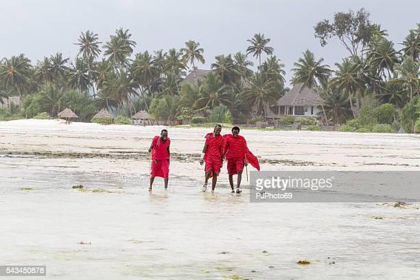 Three Masai warriors walking on the beach