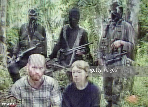 Three masked Abu Sayyaf Muslim gunmen guard kidnapped US Christian missionaries Martin Burnham and his wife Gracia Burnham at an undisclosed jungle...