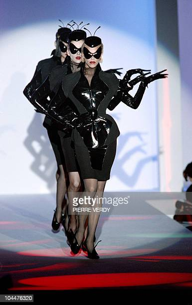 Three masked models display dark green and black leathered suits January 22 in Paris as part of Thierry Mugler's Spring/Summer haute couture...