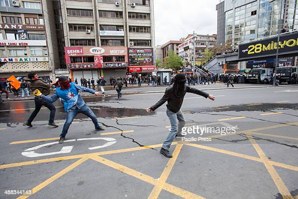 Three masked protesters one wearing a vest of the Socialist Party of the Oppressed start throwing stones at the police May Day demonstrations have...