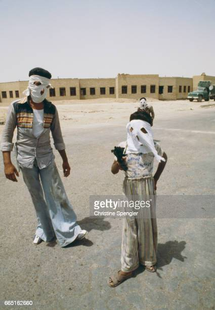 Three masked rebel fighters one of them a young boy holding a gun wait in the streets of Khorramshahr following riots between Ruhollah Khomeini's...