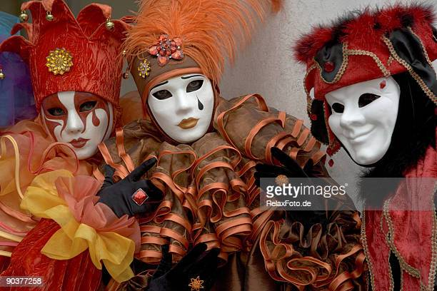 three masks with harlequin costumes at carnival in venice (xxl) - harlequin stock photos and pictures