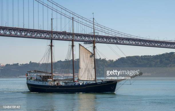 Three masted topsail steel schooner 'Príncipe Perfeito' sails with tourists on the Tagus River past 25 de Abril bridge on October 01 2018 in Lisbon...