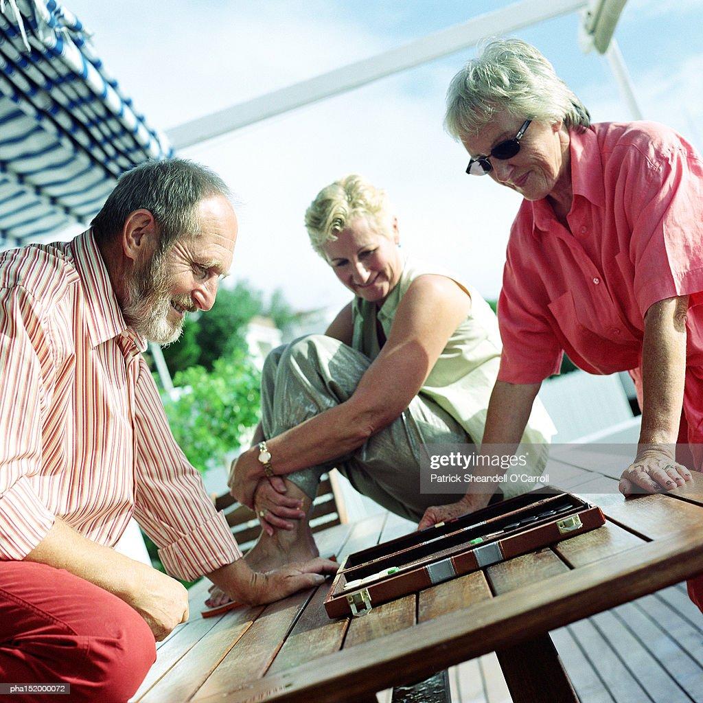 Three mature adults playing backgammon. : Stockfoto