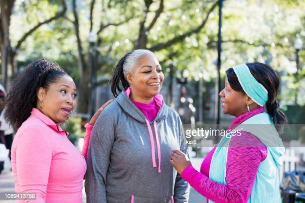 Three mature African-American women conversing