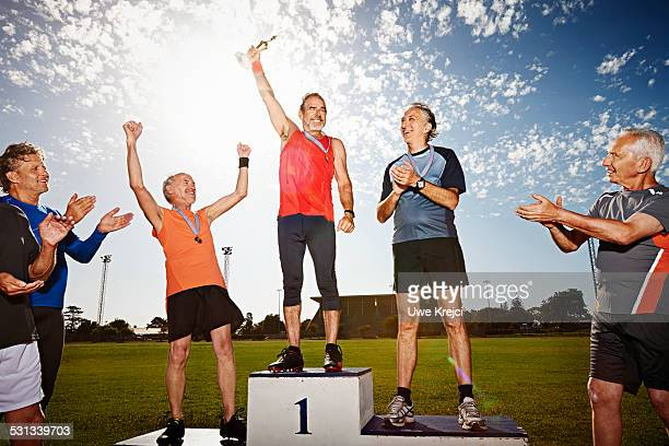 three mature athletes on podium with medals - winners podium stock pictures, royalty-free photos & images