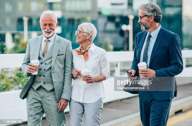 drei reife geschäftsleute, die im freien spazieren gehen - arbeitende rentner stock-fotos und bilder