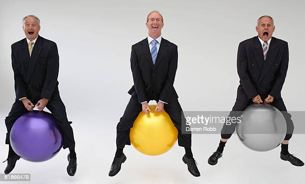 Three mature businessmen bouncing on space hoppers, laughing