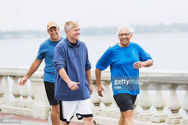 Three mature men exercising, walking on waterfront