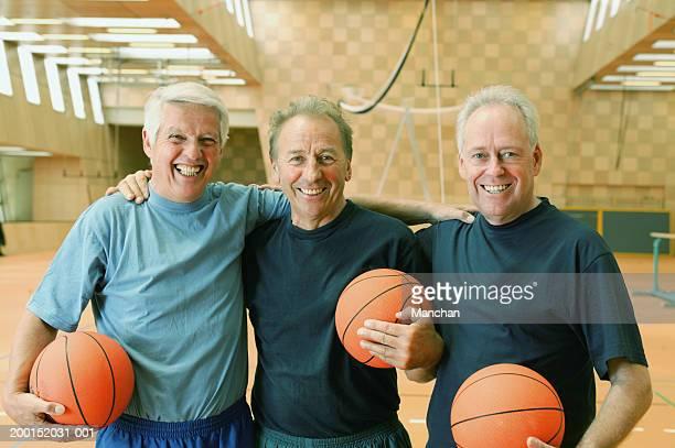 Three mature men holding basketballs in gymnasium, smiling, portrait
